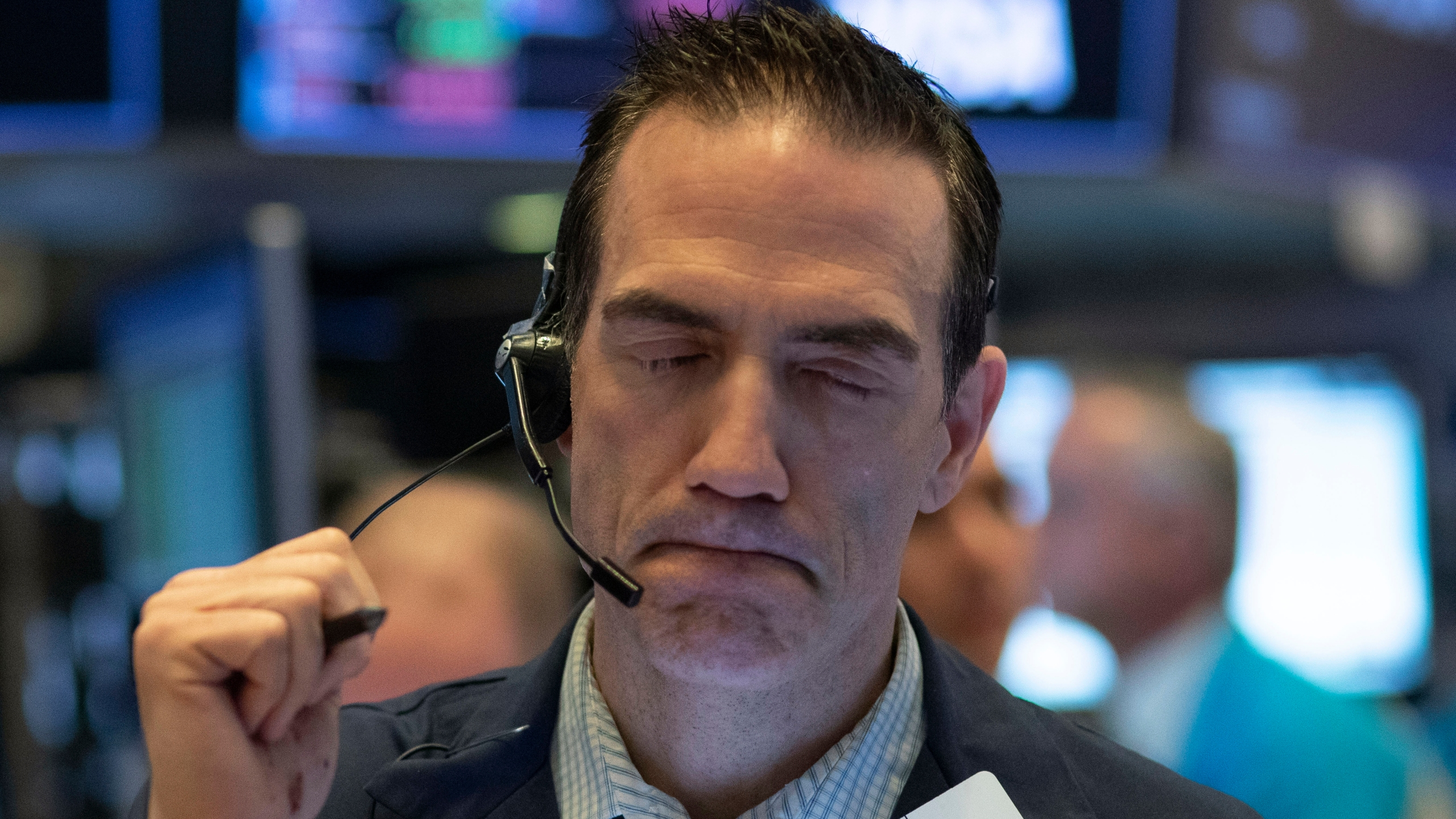 Stock trader Gregory Rowe works at the New York Stock Exchange, Wednesday, March 18, 2020 in New York. (AP Photo/Mark Lennihan)