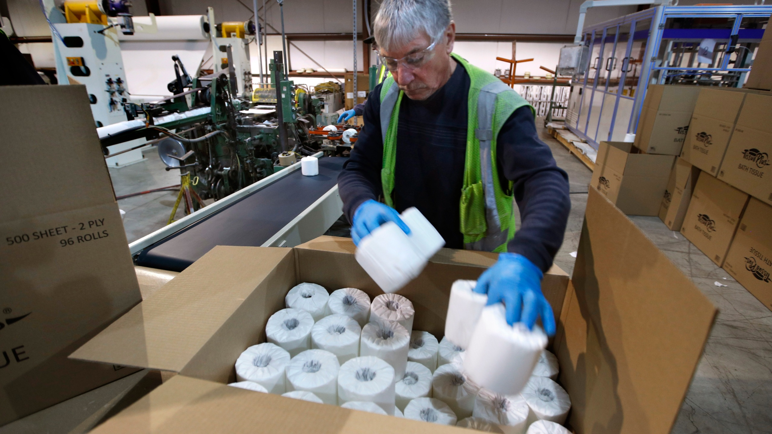 Scott Mitchell fills a box with toilet paper at the Tissue Plus factory, Wednesday, March 18, 2020, in Bangor, Maine. The new company has been unexpectedly busy because of the shortage of toilet paper brought on by hoarders concerned about the coronavirus. (AP Photo/Robert F. Bukaty)