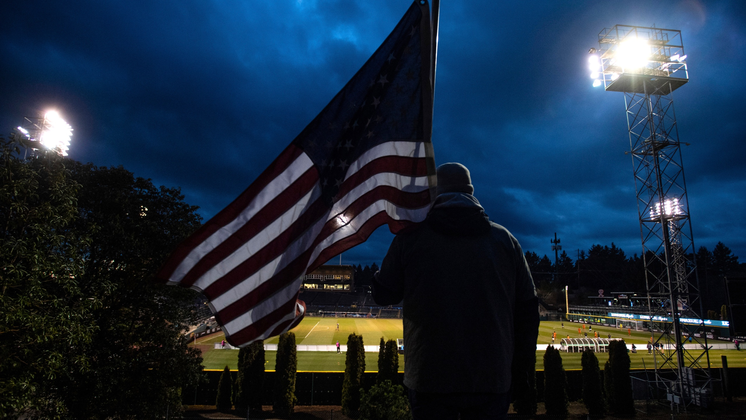 A man holds an U.S. flag as he watches the a United Soccer League match in Tacoma, Wash. on March 11. In a matter of days, millions of Americans have seen their lives upended by measures to curb the spread of the new coronavirus in mid-March. (Joshua Bessex/The News Tribune via AP)