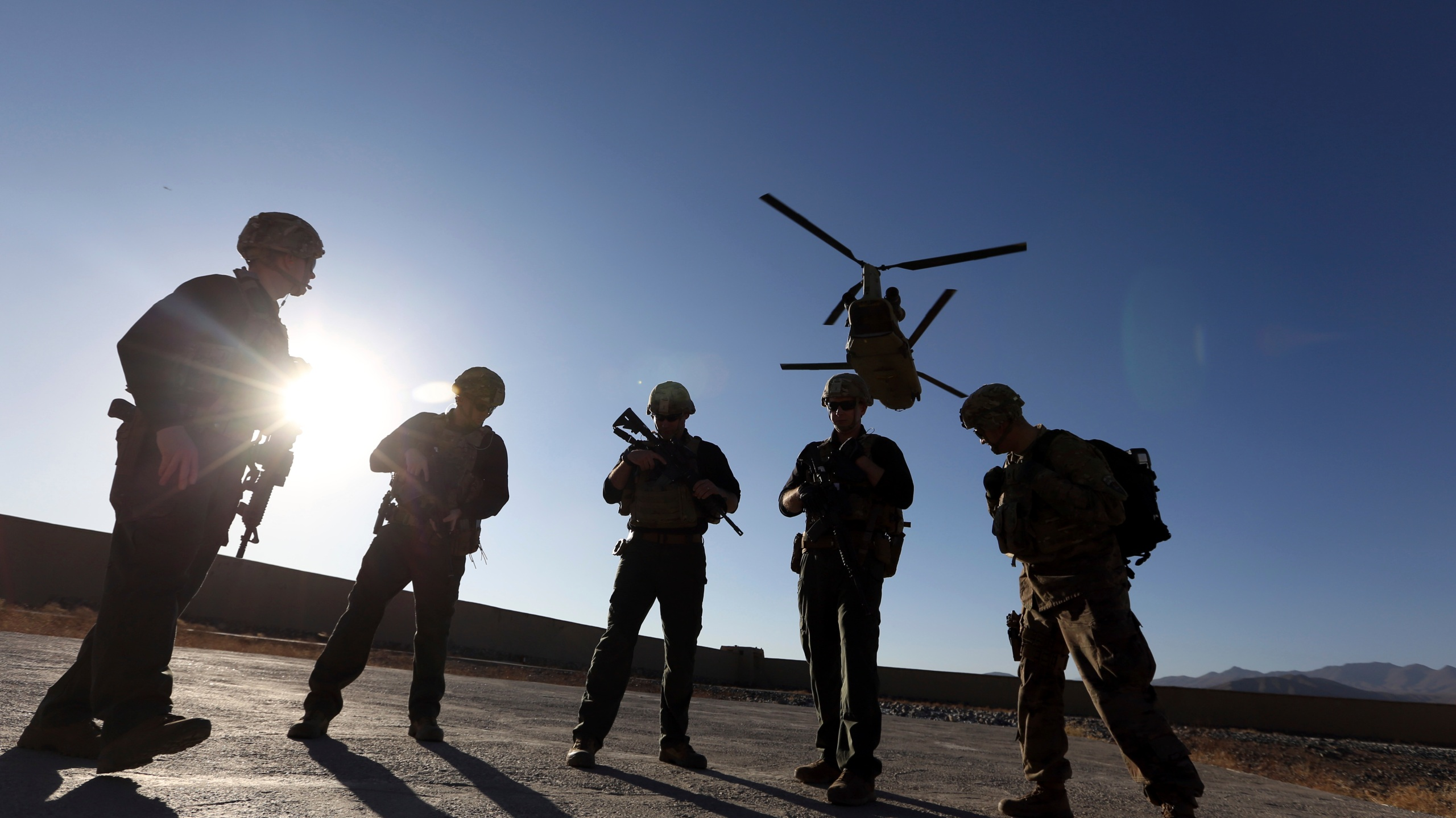 American soldiers wait on the tarmac in Logar province, Afghanistan in this Nov. 30, 2017 file photo. The U.S. is pausing movement of troops into Afghanistan and quarantining 1,500 new arrivals to country due to virus. (AP Photo/Rahmat Gul, File)