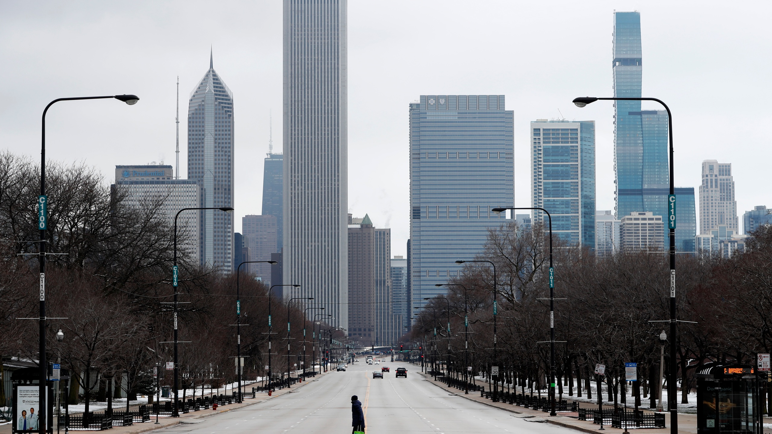 A woman walks across the usually busy Columbus Drive that splits Chicago's Grant Park in half, on the first work day since Illinois Gov. J.B. Pritzker gave a shelter in place order last week. Pritzker says Illinois is not receiving enough medical supplies in its fight against the coronavirus. (AP Photo/Charles Rex Arbogast)