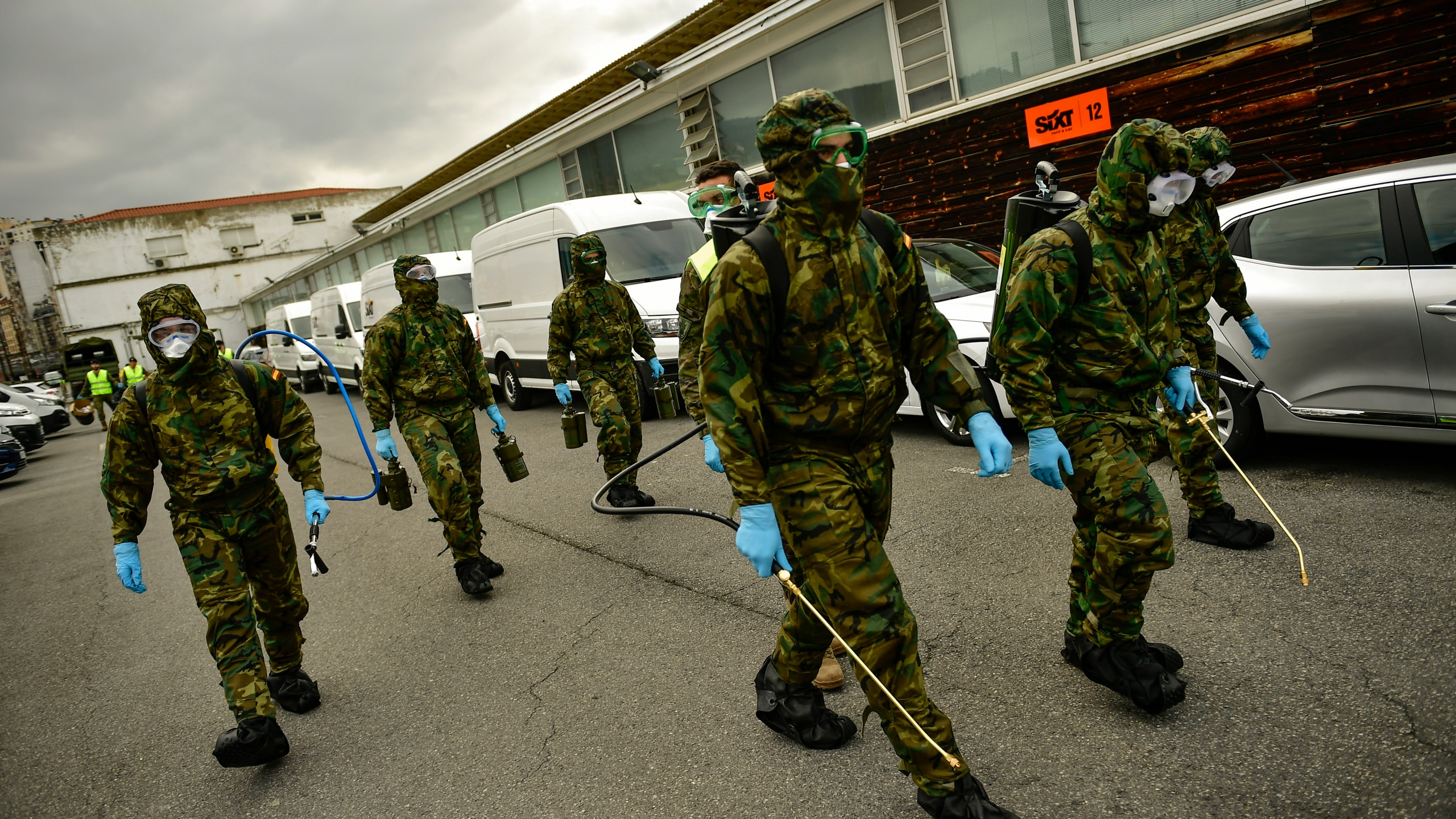 Spanish military members walk with special equipment to disinfect areas to prevent the spread of the coronavirus, arrive at Abando train station, in Bilbao, northern Spain, Monday, March 23, 2020. (AP Photo/Alvaro Barrientos)