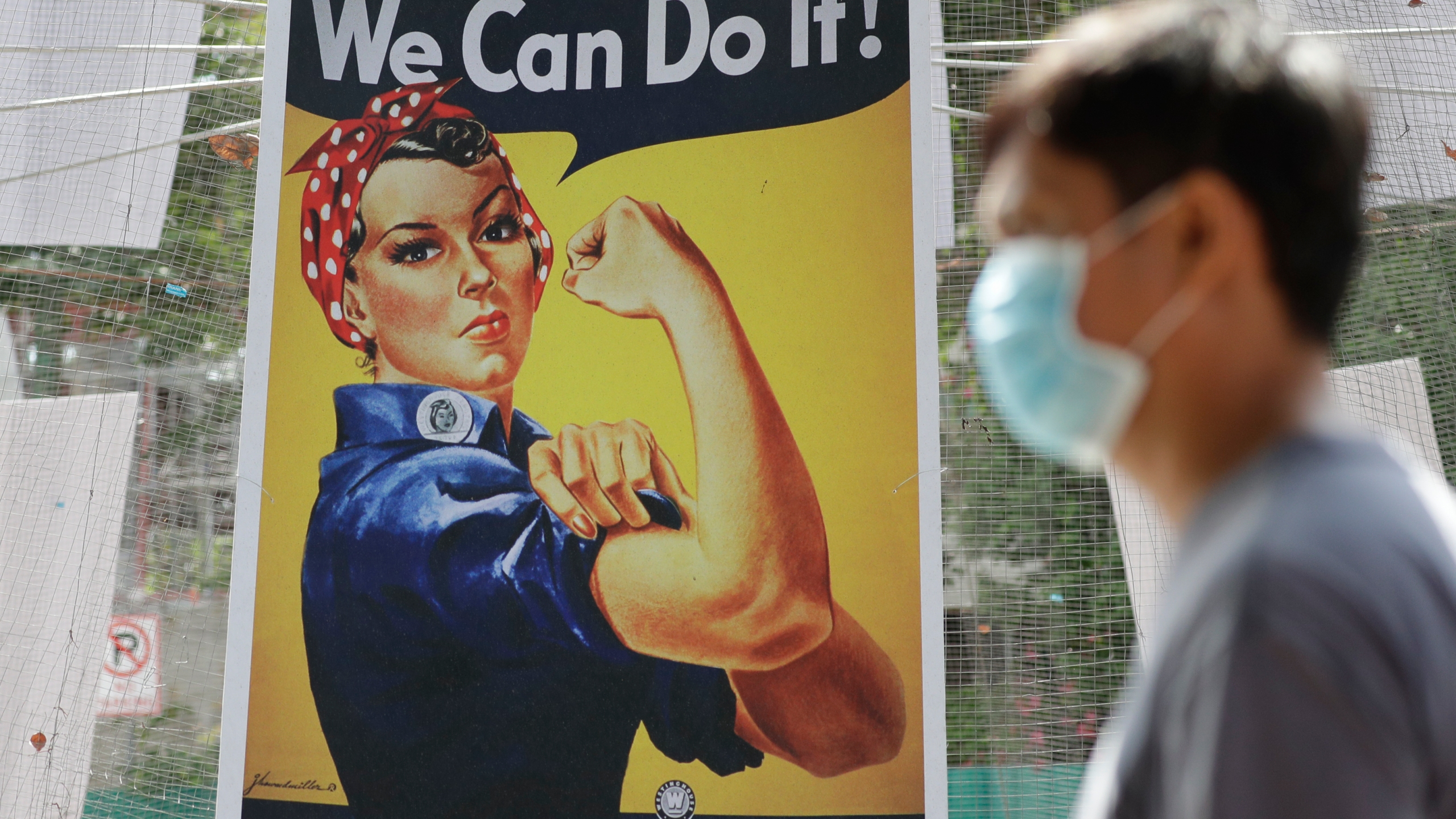 A man wearing a protective mask walks beside a poster of American WWII icon Rosie the Riveter, at the Quezon city hall where volunteers and workers help prepare food during the community quarantine aimed to prevent the spread of the new coronavirus in Manila, Philippines, Tuesday, March 24, 2020. . (AP Photo/Aaron Favila)
