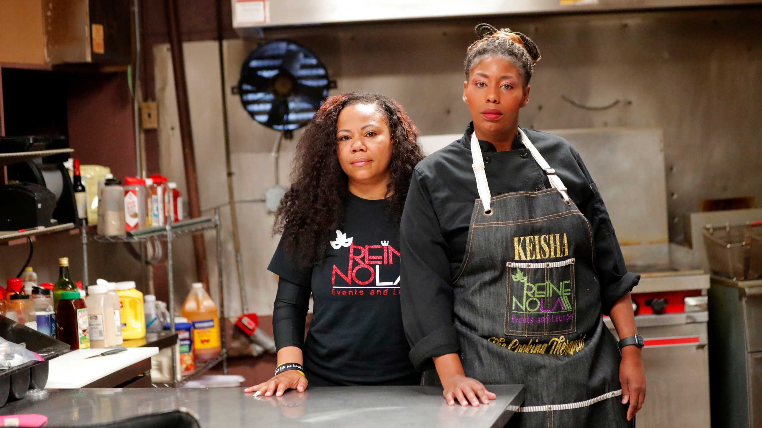 Keisha Henry, right, and her business partner Erica Norwood pose inside their lounge and catering business in New Orleans. Henry said she lost about $10,000 in revenue last week after three big functions she was slated to cater ended up canceling. Meanwhile, she still has expenses related to launching a bar and lounge six months ago. Henry said she regrettably had to lay off several employees. (AP Photo/Gerald Herbert)