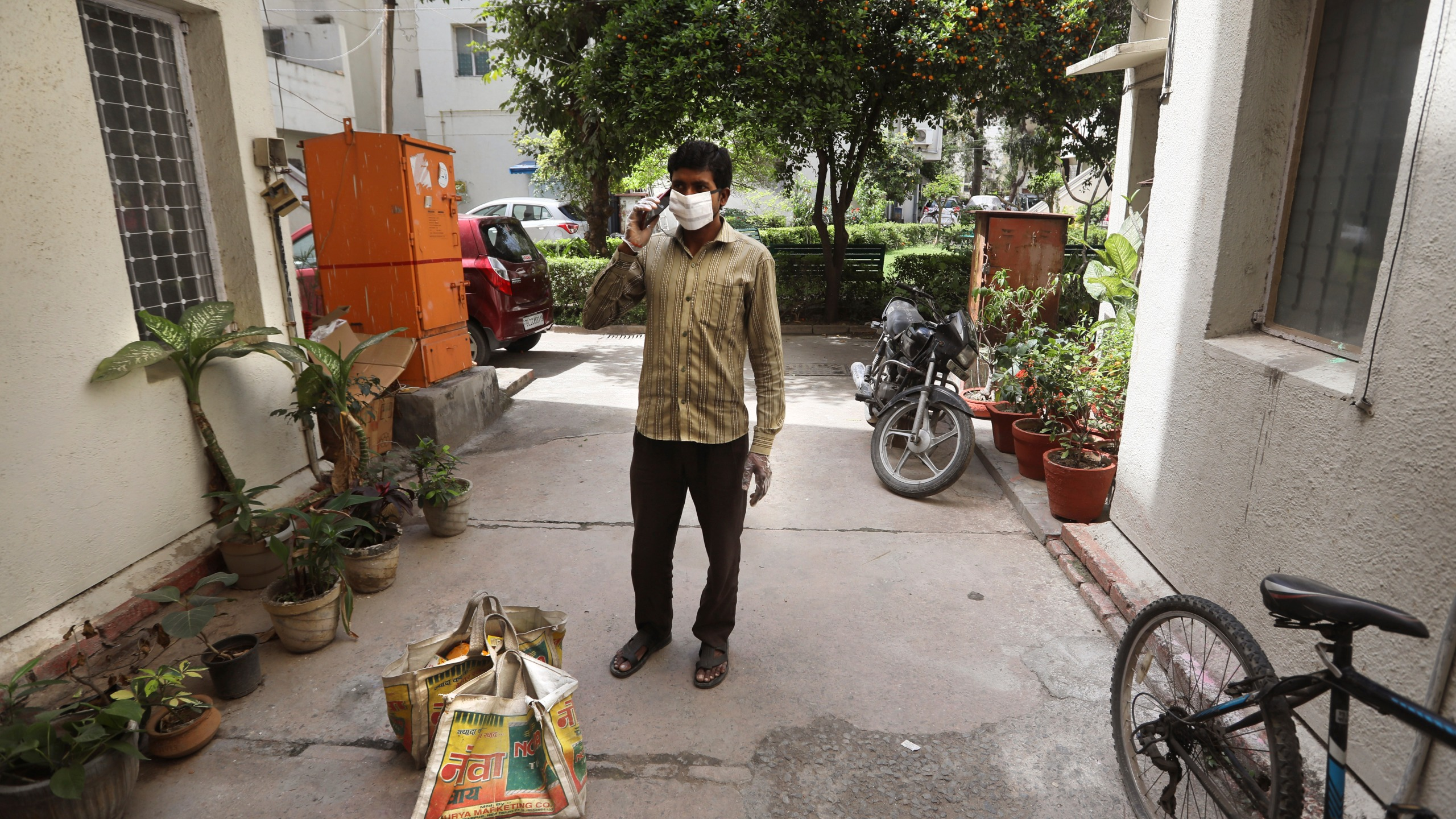 A grocery shop employee, wearing face mask as a precaution against coronavirus, calls a customer living on the second floor to come down to receive their delivery in New Delhi, India, Wednesday, March 25, 2020. The world's largest democracy went under the world's biggest lockdown Wednesday, with India's 1.3 billion people ordered to stay home in a bid to stop the coronavirus pandemic from spreading and overwhelming its fragile health care system as it has done elsewhere. (AP Photo/Manish Swarup)