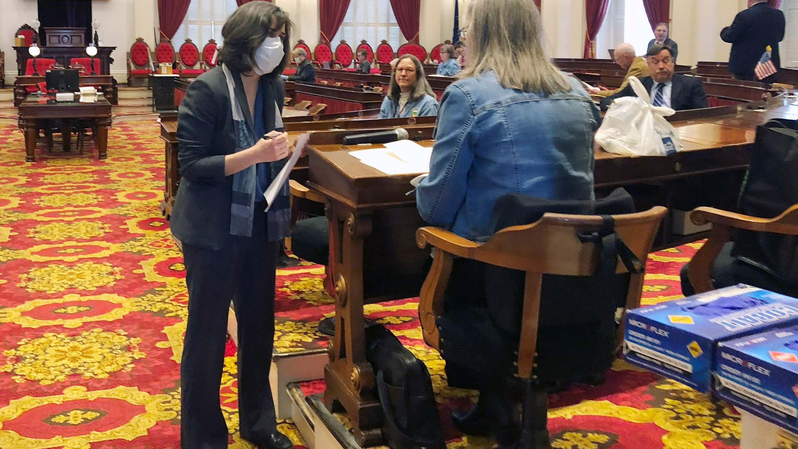 Vermont House Speaker Mitzi Johnson, left, wears a mask while talking to a lawmaker in the Vermont house chamber at the Statehouse in Montpelier, Vt. In state capitols across the U.S., lawmakers have ditched decorum and sidestepped traditional public meeting requirements in a rush to pass legislation funding the fight against the coronavirus and aiding residents affected by the widespread shut down of commerce. (AP Photo/Wilson Ring, File)