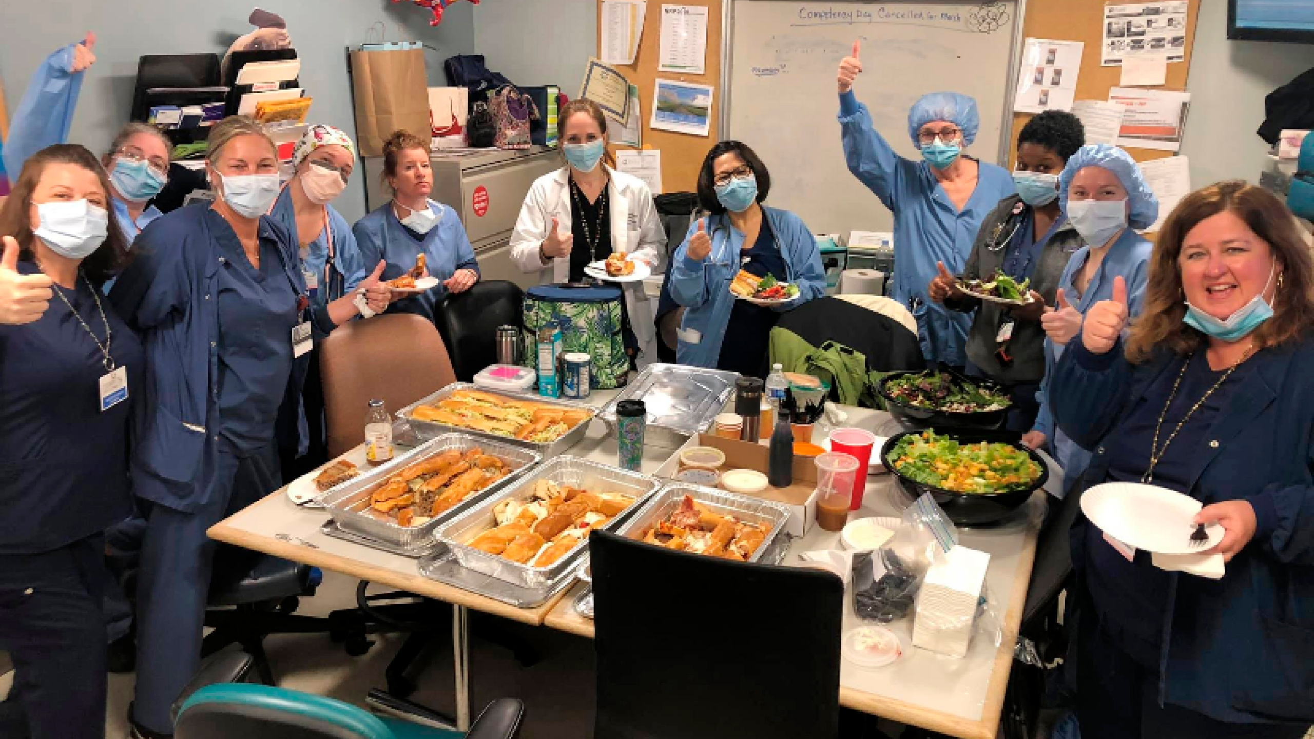 Staff members of the Hackensack Meridian Jersey Shore University Medical Center give a thumbs-up in Neptune City, N.J., as they eat a donated meal from Federico's Pizza. With restaurants closed for all but takeout orders during the coronavirus outbreak, the owners of the pizzeria could have shut down and laid off their 20 employees. Instead, the business's owners took out a $50,000 line of credit and guaranteed their workers they'll stay on the payroll for at least two months. (Courtesy of Maureen Morin via AP)