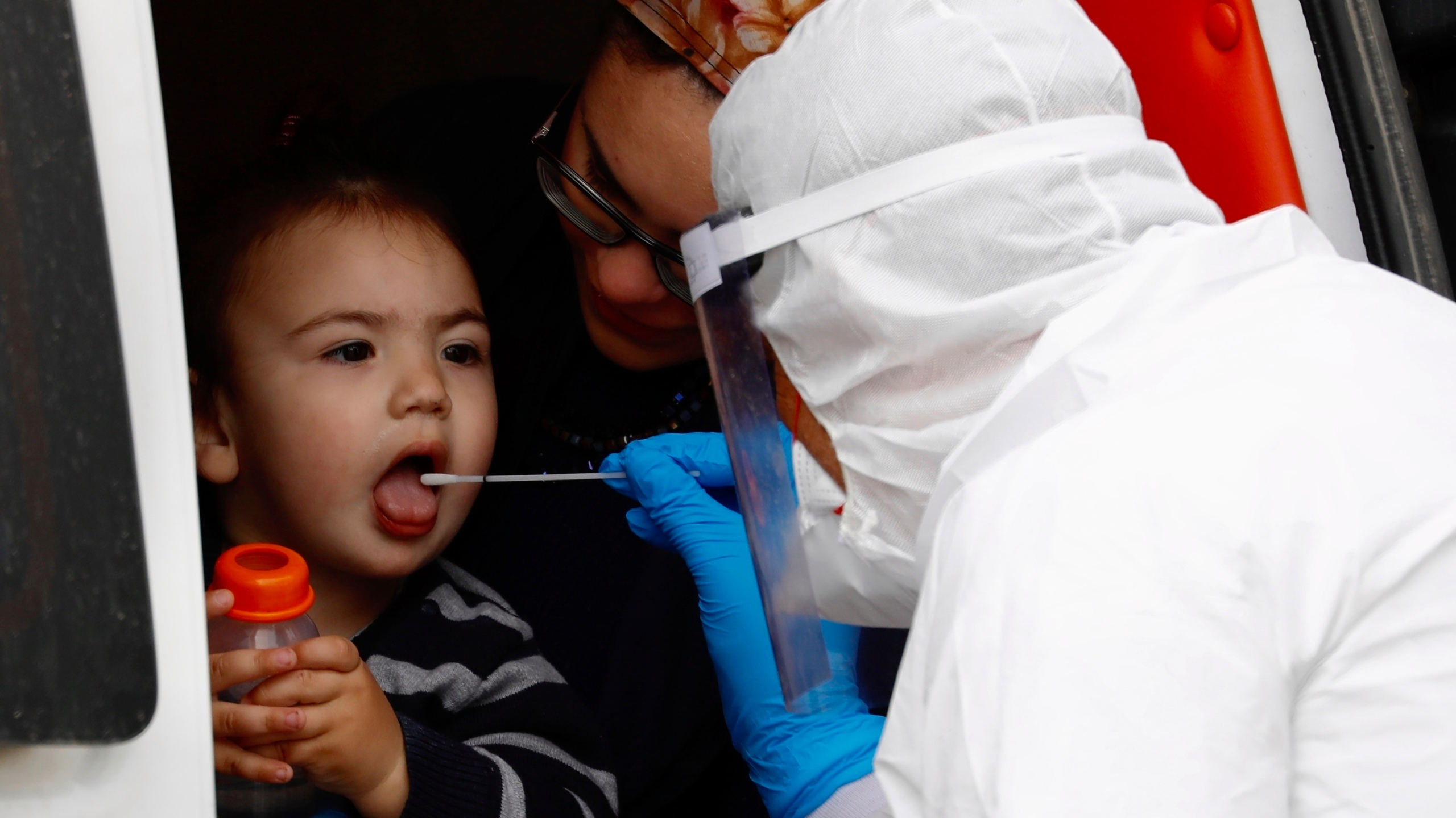 An ultra-Orthodox Jewish boy receives a COVID-19 test from medical personnel wearing protective gear as part of the government's measures to stop the spread of the coronavirus in the orthodox city of Bnei Brak, a Tel Aviv suburb, in Israel, Tuesday, March 31, 2020. (AP Photo/Ariel Schalit)