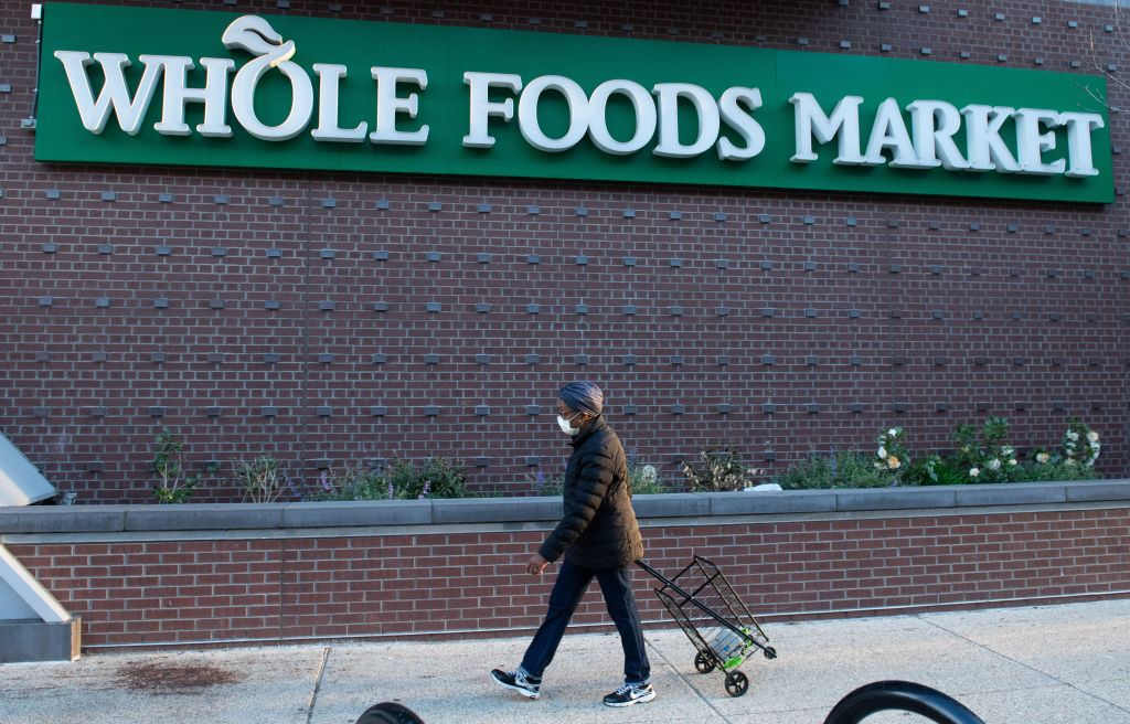 A woman walks into a Whole Foods supermarket during hours reserved for customers 60 years and older to minimize contact with others as people social distance due to the outbreak of the coronavirus, at a store location in Washington, DC, March 20, 2020. - Whole Foods, like several other retailers, is reserving some hours for customers 60 years and older to minimize contact with others as people social distance due to the outbreak of the coronavirus. (Photo by SAUL LOEB/AFP via Getty Images)