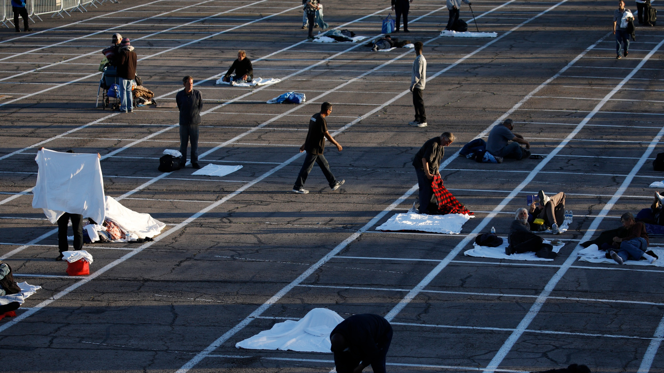 People prepare to sleep in areas marked by painted boxes on the ground of a parking lot at a makeshift camp for the homeless in Las Vegas. Officials opened part of the lot as a makeshift homeless shelter after a local shelter closed when a man staying there tested positive for the coronavirus. (AP Photo/John Locher)