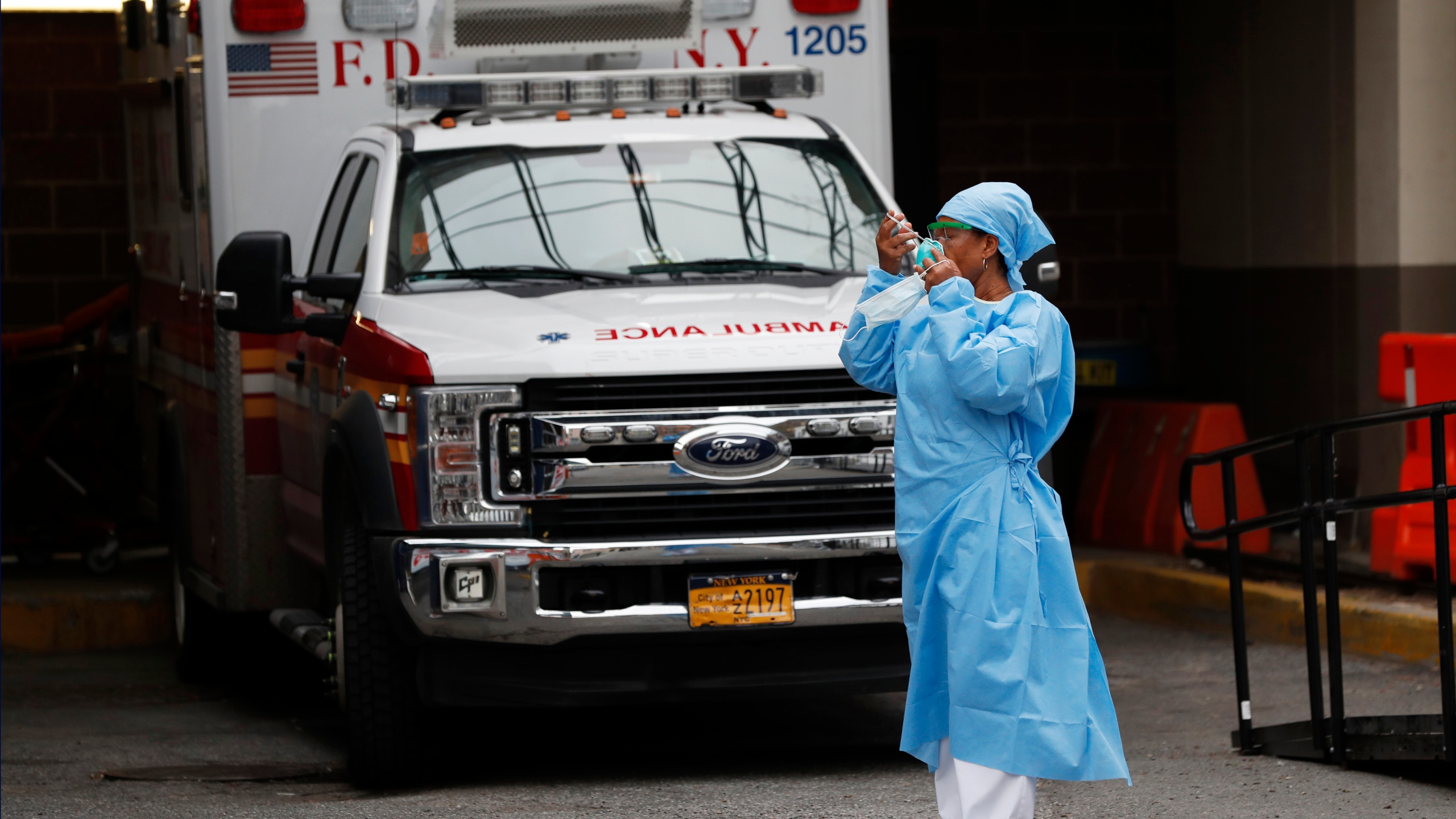 An emergency room nurse dons her face protectors after taking a break in a driveway for ambulances and emergency medical services vehicles outside Brooklyn Hospital Center's emergency room, in New York on Sunday. (AP Photo/Kathy Willens)
