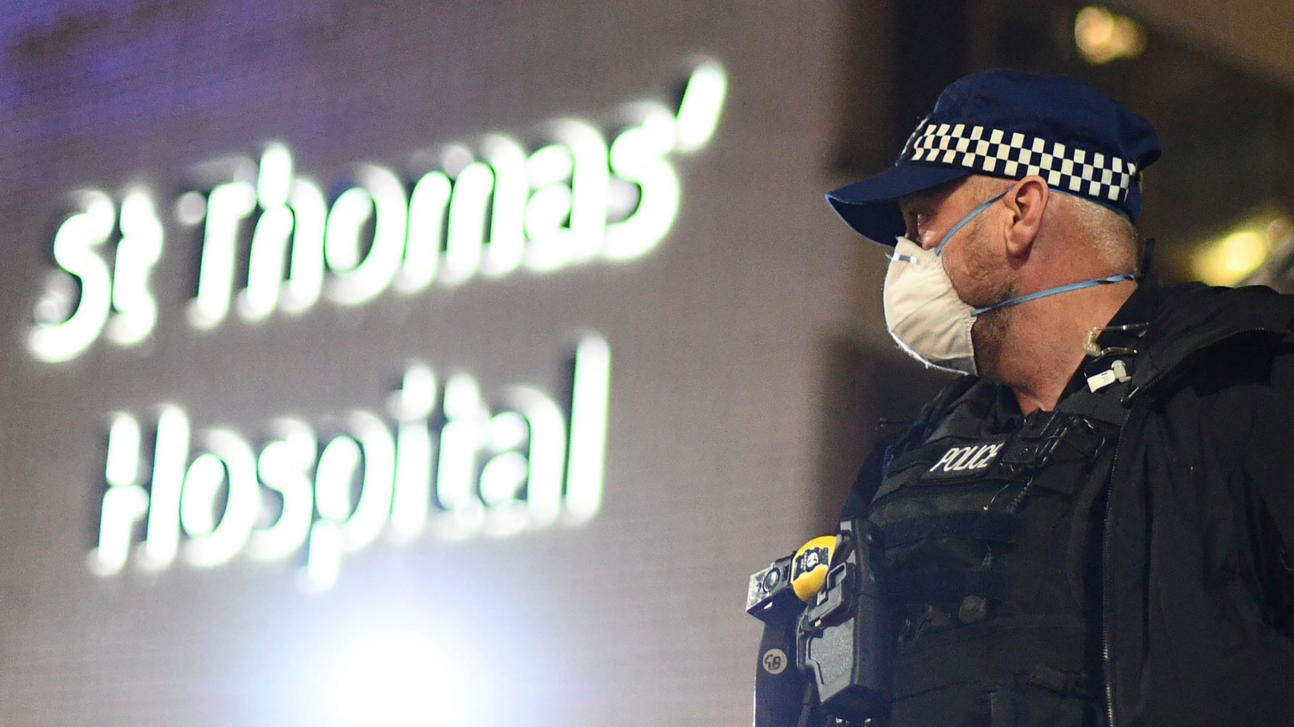 A police officer stands outside St Thomas' Hospital in central London as British Prime Minister Boris Johnson was moved to intensive care. (Victoria Jones/PA via AP)