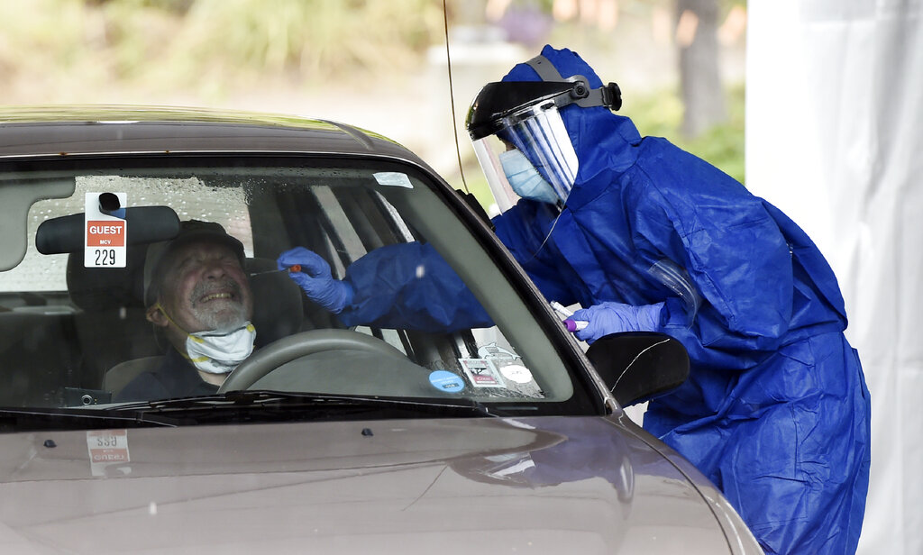 A health worker administers a coronavirus test at a drive-through testing site organized by actor Sean Penn's nonprofit organization Community Organized Relief Effort (CORE) at Malibu City Hall in Malibu, California. (AP Photo/Chris Pizzello)